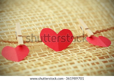 Vignette Style, Series of Valentines Card. Three Red heart paper cut with clothes pin on wooden weaving background, in very shallow focus. Image of Valentines day. - stock photo