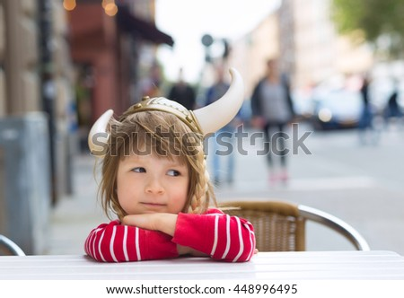 viking blond girl in red shirt in preschool age sitting at table and waiting for food in cafe outdoors, wearing costume hat with horns, smiling - stock photo