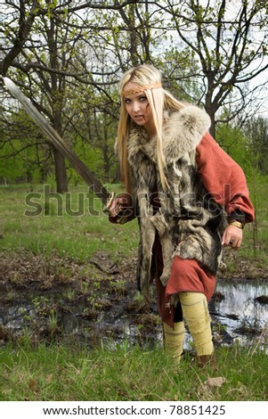 Viking girl warrior with sword in a fight - stock photo