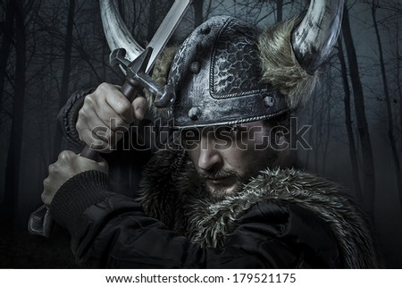 Viking warrior, male dressed in Barbarian style with sword, bearded - stock photo