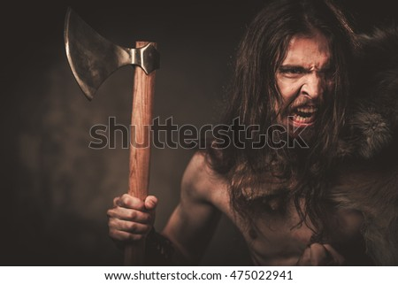 Viking with ax in a traditional warrior clothes, posing on a dark background.