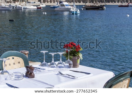 Vilfransh Sur Mer, France, on March 10, 2015. Little tables of summer cafe on the embankment. Vilfransh Sur Mer - the suburb of Nice, one of popular resorts of French riviera - stock photo