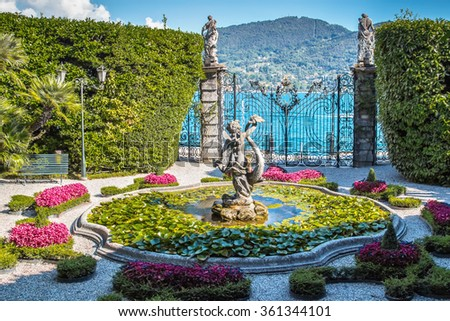 VILLA CARLOTTA, ITALY - AUGUST 02, 2015: Old fountain with stone statue in beautiful garden, villa Carlotta, Como lake, Italy. - stock photo