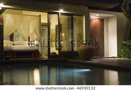 Villa in night illumination and pool before her - stock photo