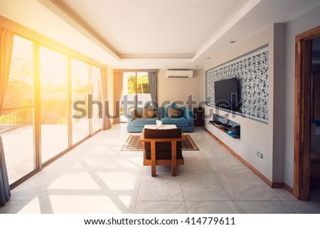 Villa interior living room. Sunlight through big window, terrace - stock photo