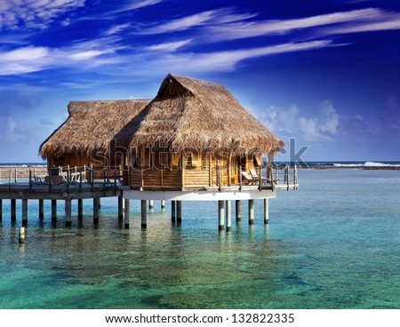 Villa on piles on water - stock photo