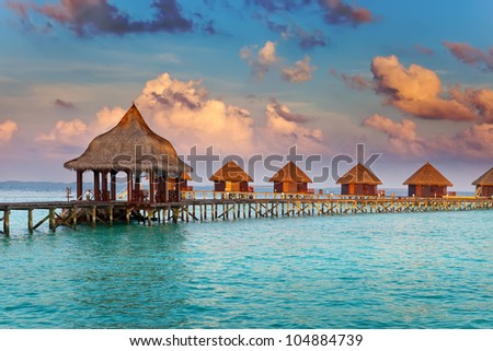 Villa on piles on water at the time sunset - stock photo