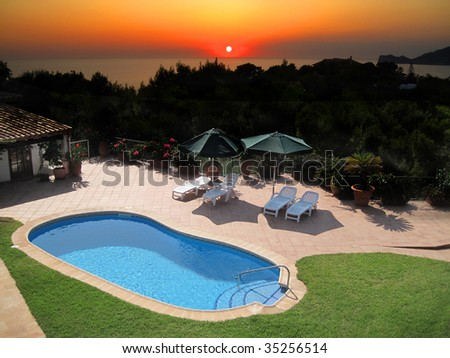 Villa With Outdoor Swimming Pool and sunset - stock photo