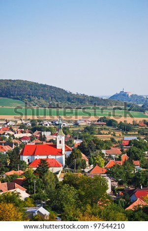 Village and rural environment with castle dominated in the background - stock photo