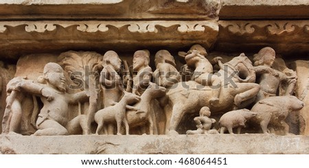 Village and rural people with animals on stone relief of Khajuraho temple, India. UNESCO Heritage site, built between 950 and 1150 in India, belong to Hinduism and Jainism.