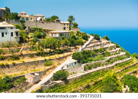 Village Banyalbufar.Traditional villa overlooking terraced vineyard and idyllic blue sea. Majorca. Balearic Islands. Spain - stock photo
