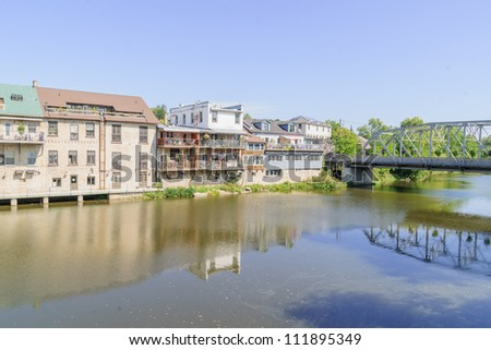 village by the riverside with road bridge - stock photo