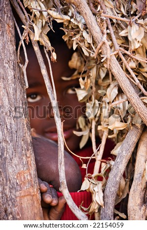 Village child hiding between the branches of an african hut front focus - stock photo