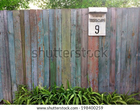 Village fence with address plate / outdoors photography of wooden fence  - stock photo