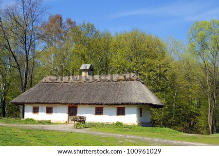 Village house in forest environment, old-fashion Ukrainian hut - stock photo