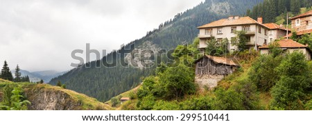 Village houses and outbuildings in the village of Mugla in coniferous forest on the steep slopes of the Rhodope Mountains in cloudy weather (Rhodopes, Bulgaria) - stock photo