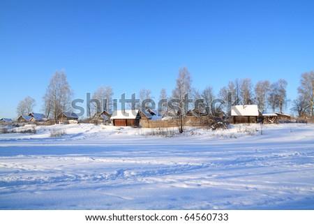 village in snow on coast river - stock photo