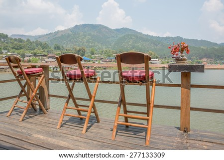 Village lakeside with a chair on the balcony.