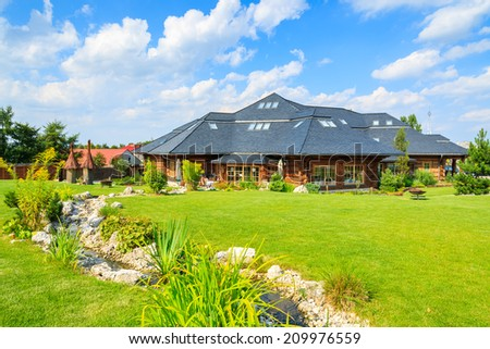 VILLAGE NEAR KRAKOW, POLAND - AUG 9, 2014:green garden of traditional restaurant building on sunny summer day. Mountain style architecture is very popular in south of Poland.