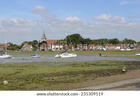 Village of Bosham in Chichester Harbour. West Sussex. England. Low tide with beached boats. People in distance - stock photo