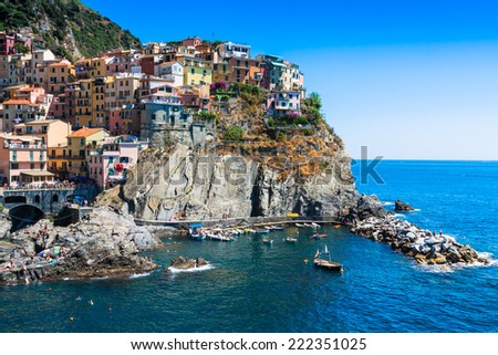 Village of Manarola with ferry, Cinque Terre, Italy - stock photo