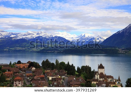 Village of Oberhofen with lake of Thun and snowy mountains, Switzerland  - stock photo