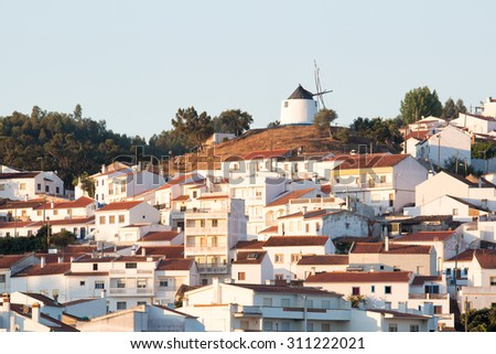 Village of Odeciexe, near the coastline in natural park costa Vicentina, the southwest coast of Portugal, early in the morning with a windmill on the top of the hill - stock photo