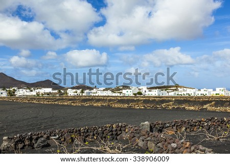 village of Tinajo with white houses and volcanoes of Timanfaya national park - stock photo