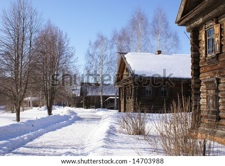 Village street of old wooden nicely decorated houses, winter