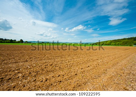 Village Surrounded by Yellow Fields of Lucerne and Plowed Field, Germany - stock photo