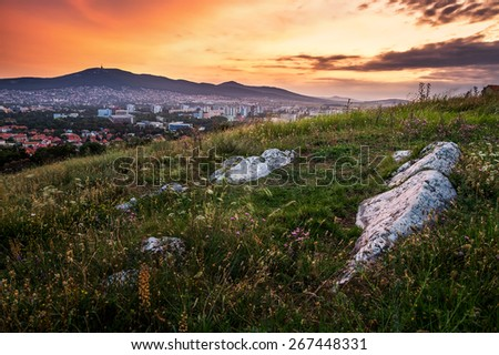 Village under a Hill at Sunset. Meadow with Flowers and Rocks in Foreground. - stock photo