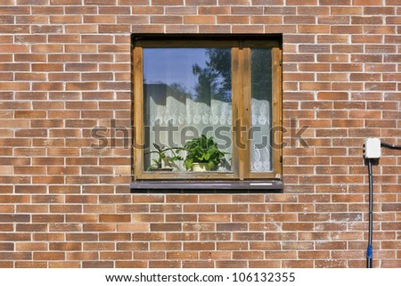 Village window with indoor flowers on red brick wall in mass rural home front view. Sunny summer day - stock photo