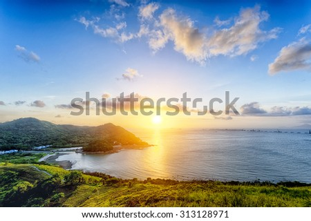 Village with beautiful sunset over hong kong coastline. View from the top of mountain - stock photo