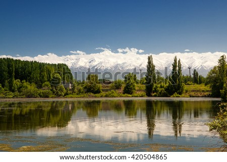 Village with pasture near the blue river - stock photo