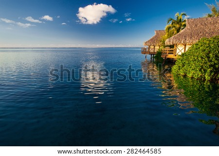 Villas in a tropical resort and blue sky reflected in the ocean