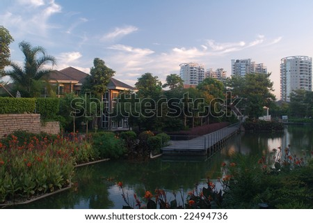 Villas in garden with flowers and lake in the foreground and new buildings in the background.This a new residential district for rich man in China