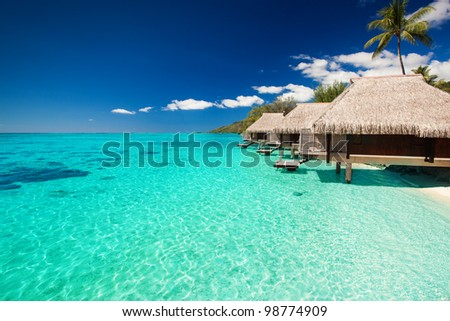 Villas on the green tropical beach with steps into water - stock photo