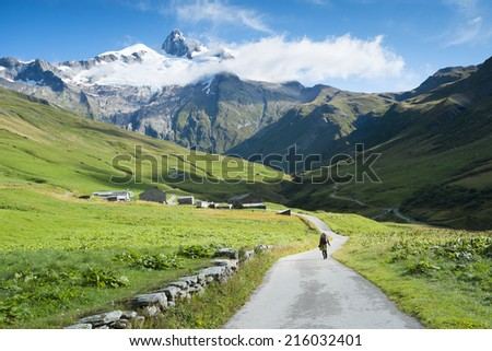 VILLE DES GLACIERS, FRANCE - AUGUST 27: Hiker walking towards Glacier Needles. The region is a stage at the Mont Blanc tour, which crosses three countries. August 27, 2014 in Ville des Glaciers. - stock photo