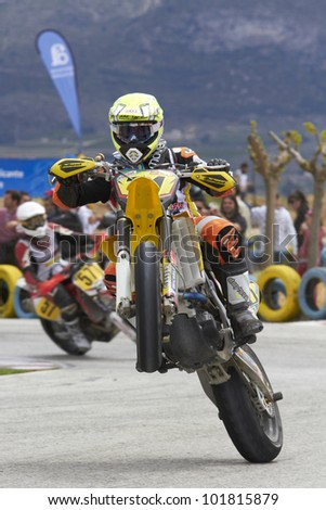 VILLENA, SPAIN - MAY 29: An unidentified pilot pulls a wheelie at in the Spanish championship of supermotard on May 29, 2012, Villena Spain - stock photo