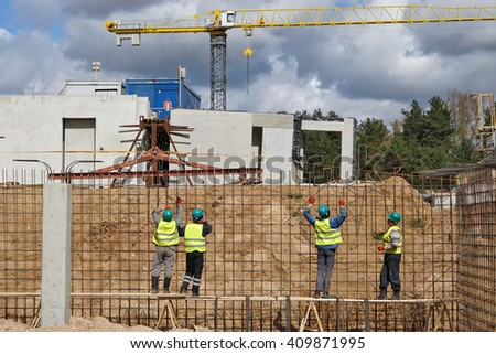 VILNIUS, LITHUANIA - APRIL 23, 2016:  Builders mount metal fittings in a ditch of the house under construction. It is the new quickly growing residential area of the Lithuanian capital - Pilaite - stock photo