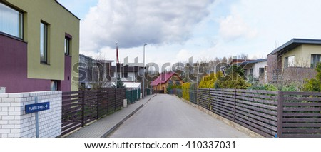 VILNIUS, LITHUANIA - APRIL 23, 2016:  The perspective of  new city area -  Pilate -  is built up with modern cottages and country houses. The name of the street on a blue arrow - Sodu (Garden) Fourth