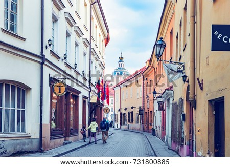 Vilnius, Lithuania - April 1, 2017: Tourists on ancient street in the Old city center in Vilnius, Lithuania