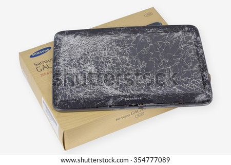 VILNIUS, LITHUANIA - DECEMBER 23, 2015:  Samsung Galaxy brand tablet with broken screen lie on table in repair service center. In 2015 Samsung sold more than 70 million phones and tablets - stock photo
