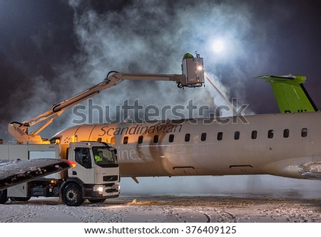 VILNIUS, LITHUANIA- FEBRUARY 12, 2016: Ground crew provides de-icing of Scandinavian Airlines CRJ-900 before take off at Vilnius airport on February 12. - stock photo