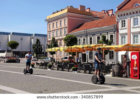 VILNIUS, LITHUANIA - JULY 19, 2015: People on Segways at The Town Hall Square in Vilnius, Lithuania. Vilnius is known for its Old Town of beautiful architecture, declared a UNESCO World Heritage Site.