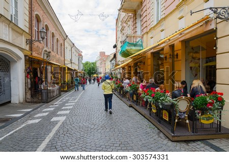 VILNIUS, LITHUANIA - JULY 10, 2015: Unidentified people walk along Pilies Street, which is popular place of walks and tourist route with scenic city views, numerous attractions, cafes, souvenir shops - stock photo