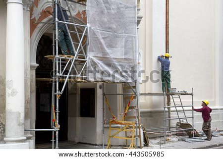 Vilnius, Lithuania - June 20, 2016: Construction workers in scaffolding restoration of the old building in Oldtown