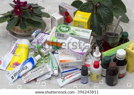 VILNIUS, LITHUANIA - MARCH 26, 2016:  Life of the elderly person depends on drugs. Various tablets, pills, ointments and tinctures lie on a little table at a bed. - stock photo