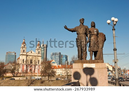 """Vilnius, Lithuania - March 16, 2015: Soviet realism sculptural group """"Agriculture"""" on the Green bridge - the oldest bridge in Vilnius, Church of St. Raphael the Archangel on background. - stock photo"""