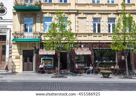 VILNIUS, LITHUANIA - MAY 5, 2015. Green spring street of Vilnius (Gedimino avenue) with young trees and people sitting at cafe in sunny day.